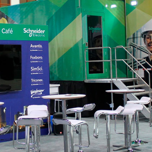 Trade show exhibit for Schneider Electric featuring a hanging banner, monitor wall and cocktail chairs.